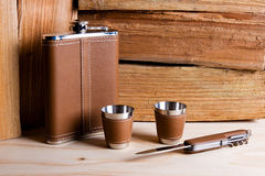 Hip metal flask, cups and knife on wooden background. Stock Images