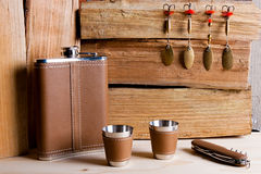 Hip metal flask, cups and knife on wooden background. Royalty Free Stock Image