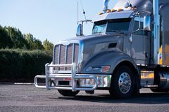 Hip powerful gray glossy big rig semi truck with grille guard an. Hip powerful gray glossy professional American big rig reliable semi truck with grille guard Stock Photography