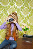 Hip retro little girl shooting vintage camera. Hip retro little girl shooting photo with vintage camera on wallpaper Royalty Free Stock Photos