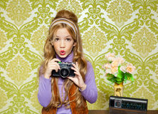 Hip retro little girl shooting on vintage camera. Hip retro little girl shooting photo with vintage camera on wallpaper Stock Image