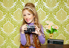 Hip retro little girl shooting on vintage camera. Hip retro little girl shooting photo with vintage camera on wallpaper Stock Photos