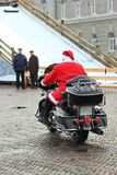 Hip Santa Clause saying good bye and going away on a motorbike Royalty Free Stock Image