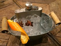 Hip screwdriver cocktail in the flask severing on the ice bucket decorate with orange skin and star anise on wood table Royalty Free Stock Image