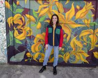 Hip sixteen year old girl in front of a garage door mural in South Philadelphia. Pictured is a hip sixteen year old girl posing in front of a garage door mural Royalty Free Stock Image