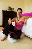 Hip woman. An elegant woman sitting on a cushion Royalty Free Stock Images