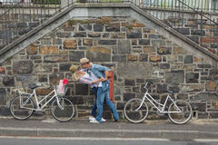 Hip young couple dancing by brick wall with their bikes Royalty Free Stock Images