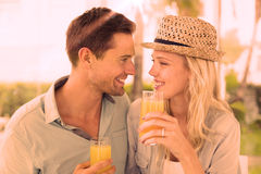 Hip young couple drinking orange juice together Stock Images