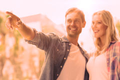 Hip young couple looking at something and pointing Royalty Free Stock Photography