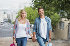 Hip young couple on shopping trip walking uphill Royalty Free Stock Photography