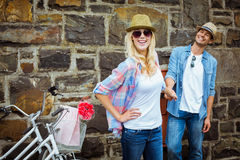 Hip young couple standing by brick wall with their bikes Royalty Free Stock Photos