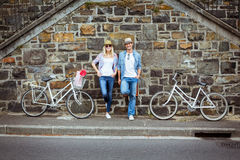 Hip young couple standing by brick wall with their bikes Stock Photos
