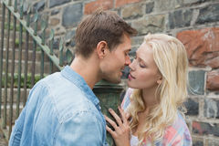 Hip young couple standing by railings about to kiss Royalty Free Stock Images