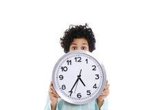 Hipanic-Frau, die große Uhr auf ihrem Gesicht hält Stockfotografie