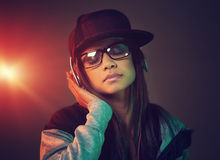 Hiphop woman. Portrait of trendy woman listening to music on headphones hiphop fashion Stock Photography