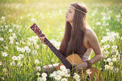 Hipis kobieta z gitarą w lato łące Zdjęcia Royalty Free