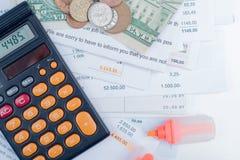 Hipoteca y facturas de servicios públicos, monedas y billetes de banco, calculadora Imágenes de archivo libres de regalías