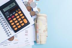 Hipoteca y facturas de servicios públicos, monedas y rollo de billetes de banco, calcula Imagen de archivo