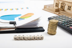 HIPOTEQUE a palavra escrita no bloco de madeira, em moedas douradas e em clipbord com carta, casa modelo Imagens de Stock