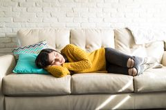 Tired Woman Sleeping On Sofa. Hippe woman lying on white comfortable sofa at home stock photo