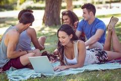 Hippie à l'aide de l'ordinateur portable dans le parc Photos libres de droits