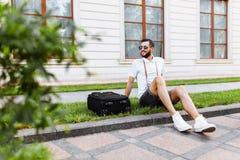 Hippie élégant avec une valise et un appareil-photo se reposant sur la pelouse photo stock