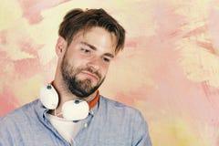 Hippie élégant observé par bleu avec le smartphone Chansons de écoute adolescentes gaies du DJ par l'intermédiaire des écouteurs image stock