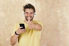 Hippie élégant observé par bleu avec le smartphone Chansons de écoute gaies du DJ par l'intermédiaire des écouteurs image libre de droits