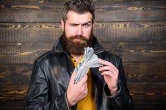 Hippie-Abnutzungslederjacke des Mannes grobe bärtige und Bargeld halten Mann geben Bargeldbestechungsgeld Reichtum und Wohl stockfotos