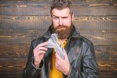 Hippie-Abnutzungslederjacke des Mannes grobe b?rtige und Bargeld halten Mann geben Bargeldbestechungsgeld Reichtum und Wohl lizenzfreies stockbild
