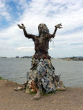 Hippie art. A statue of a woman with her hands pointing upward built of driftwood and construction waste near Berkley California. The Bay in the background Stock Photos