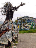 Hippie art. A statue of a woman with her hands upwards built from driftwood and construction waste near Berkley California. Graffiti in the background Royalty Free Stock Photography