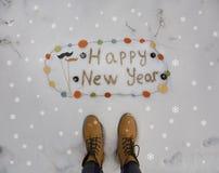 Hippie-Aufschrift guten Rutsch ins Neue Jahr geschrieben auf den Schnee und die gelben Stiefel Lizenzfreie Stockfotos