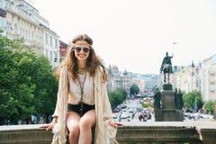 Hippie-aussehende Frau, die auf Geländer auf Wenceslas Square sitzt Lizenzfreie Stockbilder