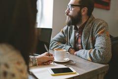 Hippie avec la barbe avec le smartphone et l'ordinateur portable sur la table donnant dedans Images stock