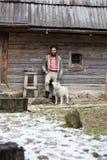 Hippie avec le chien devant la maison en bois Photo stock
