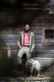 Hippie avec le chien devant la maison en bois Images stock