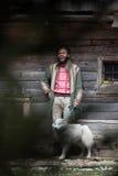 Hippie avec le chien devant la maison en bois Photos stock