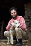 Hippie avec le chien devant la maison en bois Image libre de droits