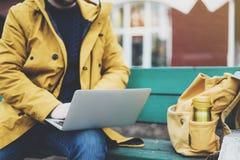 Hippie avec le sac à dos jaune, veste, chapeau, tasse de café thermo utilisant la rue ouverte d'ordinateur portable d'ordinateur  photos libres de droits