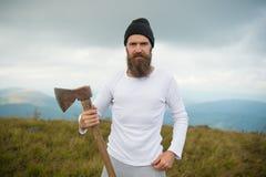 Hippie barbu d'homme avec le support de hache sur le paysage de montagne photos libres de droits