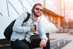 Hippie barbu de sourire moderne avec le sac à dos noir, les écouteurs dans des oreilles et la tasse thermo avec du café à disposi image stock