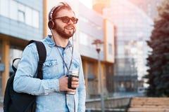 Hippie barbu de sourire moderne avec le sac à dos noir, les écouteurs dans des oreilles et la tasse thermo avec du café à disposi images libres de droits