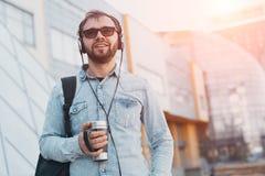 Hippie barbu de sourire moderne avec le sac à dos noir, les écouteurs dans des oreilles et la tasse thermo avec du café à disposi photo stock