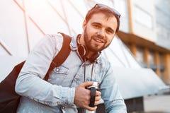 Hippie barbu de sourire moderne avec le sac à dos noir, les écouteurs sur le cou et la tasse thermo avec du café à disposition photos libres de droits