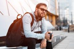 Hippie barbu de sourire moderne avec le sac à dos noir, les écouteurs sur le cou et la tasse thermo avec du café à disposition photo stock