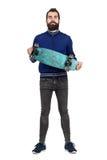 Hippie barbu fier portant et montrant la planche à roulettes à l'appareil-photo Images libres de droits