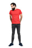 Hippie barbu sérieux dans le T-shirt rouge avec des mains dans le sien poche de dos regardant vers le bas images libres de droits