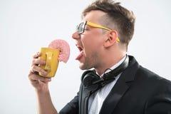Hippie beau du DJ mangeant le beignet de sa tasse dessus Image stock