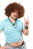 Hippie with beerbelly. Old hippie with beerbelly hanging over his jeans making the peace sign Stock Photo